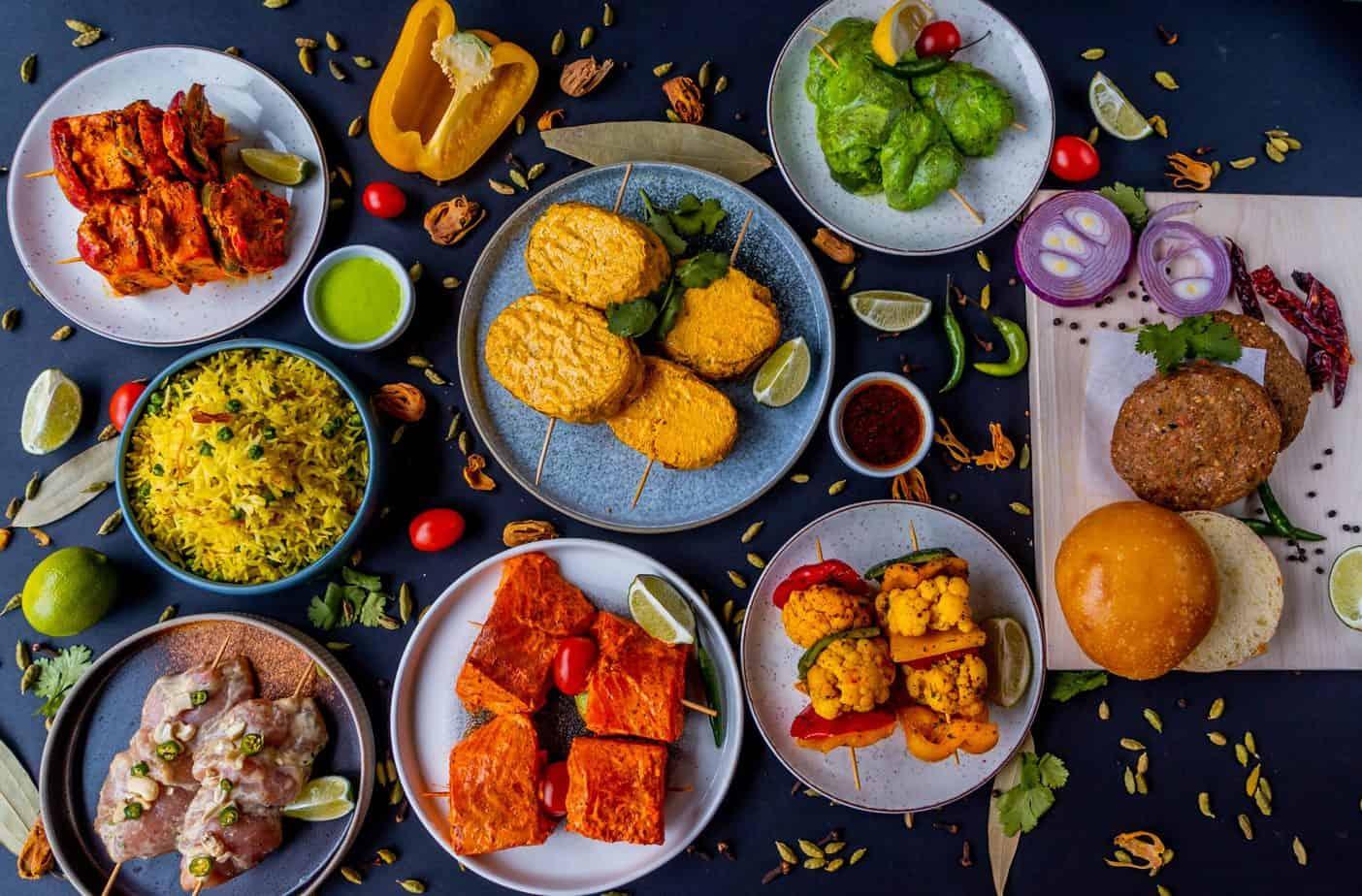 Boîte-Repas BBQ à l'indienne incluant des burgers Kebab, des brochettes de poulet Hariyali et de poulet Malai, des brochettes et de saumon Tikka et de Légumes Tandoori ainsi que des plats d'accompagnement et des condiments